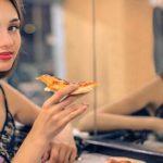 девушка ест перед зеркалом